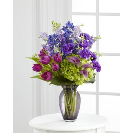 Clear glass vase with tulips, delphinium, calla lilies, purple carnations, lavender larkspur and green hydrangea